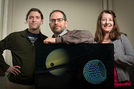Graduate student James Stevenson, astronomer Jonathan Lunine and chemical engineer Paulette Clancy, with a Cassini image of Titan in the foreground of Saturn, and an azotosome, the theorized cell membrane on Titan